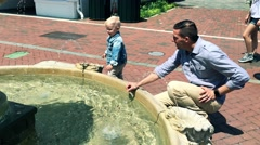 Dad and Son Play by the Water Fountain Stock Footage