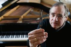 Piano tuner holding tuning fork - stock photo