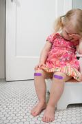 Crying girl with plasters on knees Stock Photos