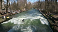 People surfing in Eisbach at english garden in Munich Stock Footage