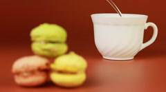 Cup of coffee with macaroons on a brown background. Stock Footage