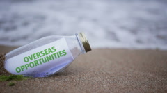 Overseas. opportunities written on a message washed ashore Stock Footage