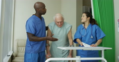 4K Caring medical workers in hospital assisting elderly man in a private room Stock Footage