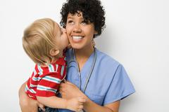 Little boy kissing nurse Stock Photos