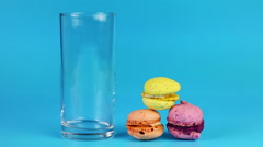 Glass of milk and macaroon on blue background Stock Footage
