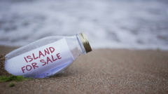 Island for sale written on a message washed ashore Stock Footage