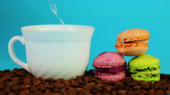 Cup of coffee on beans and macaroon on a blue background. Stock Footage