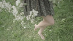 Girl with bare feet on the grass - stock footage