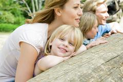 Family leaning on a log - stock photo