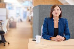 Businesswoman looking away while sitting at her office cubicle d - stock photo