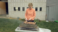 Girl cooks barbeque skewers with meat on brazier Stock Footage