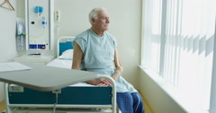 4K Portrait of smiling elderly patient sitting on his bed in hospital room - stock footage