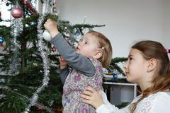 Side view of big sister helping girl decorate christmas tree Stock Photos