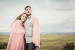 Romantic young couple on hilltop wrapped in pink blanket, Cody, Wyoming, USA Stock Photos