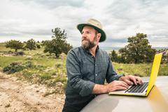 Mature man using laptop on car bonnet, Cody, Wyoming, USA Stock Photos