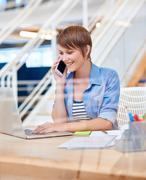 Smiling young woman on phone with laptop in modern office - stock photo