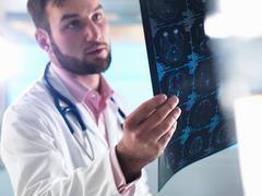 Junior doctor examining a brain scan in hospital Stock Photos