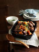 Middle eastern oxtail stew in serving dish with wooden serving spoon Stock Photos