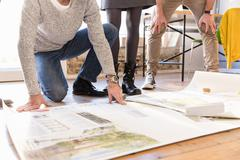 Low section of architects discussing blueprint on office floor Stock Photos