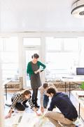 High angle view of architects on office floor discussing blueprint Stock Photos