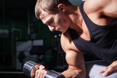 Close-up of bodybuilder doing concentration curls - stock photo