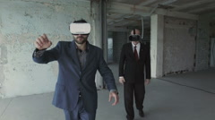 Businessmen in oculus rift watching project of future building Stock Footage