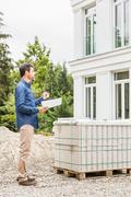 Full length side view of architect holding plans looking at house exterior - stock photo
