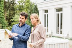 Architect discussing paperwork with homeowner looking away Stock Photos