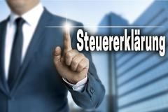 steuererklaerung (in german tax declaration) touchscreen is operated by busin - stock photo