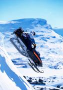 Snowboarder jumping on a skidoo. - stock photo
