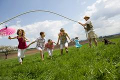 Happy family jump roping in countryside Stock Photos