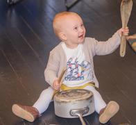 Toddler banging saucepan with kitchen utensils Stock Photos