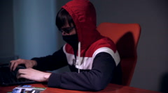 Male hacker works on a computer with data on screens in a dark room - stock footage