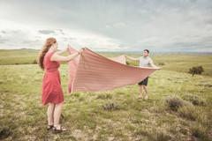 Young couple on hilltop folding pink blanket, Cody, Wyoming, USA Stock Photos