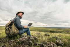 Mature male hiker sitting on rocks with laptop looking out to landscape, Cody, - stock photo