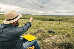 Male hiker pointing out to landscape, Cody, Wyoming, USA - stock photo