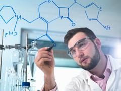Scientist illustrating antibiotic chemical formula in laboratory for - stock photo