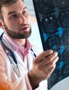 Young male junior doctor examining a brain scan in hospital Stock Photos