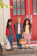 Portrait of elementary schoolboy and girls standing at elementary school doorway Stock Photos