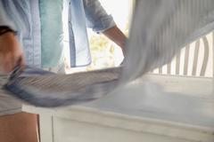 Woman laying cloth over table - stock photo
