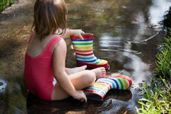 Child in wellies sitting in puddle of water Stock Photos