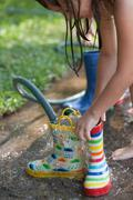 Girl filling wellies with water from hose Stock Photos