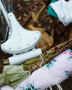 High angle close up of bicycle seat with umbrella and quilt on bicycle rack - stock photo