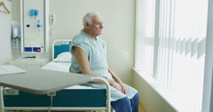 4K Portrait of smiling elderly patient sitting on his bed in hospital room Stock Footage