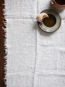 Half eaten bread roll on plate on muslin cloth Stock Photos