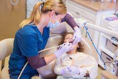 High angle view of girl in dentist chair having dental examination - stock photo