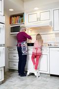Rear view of girl and grandmother stirring saucepan at kitchen hob Stock Photos