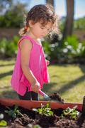 Young girl in garden, digging with trowel Stock Photos