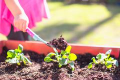 Young girl in garden, digging with trowel, mid section Stock Photos