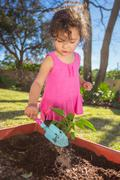 Young girl in garden, planting plant in tub, holding trowel - stock photo